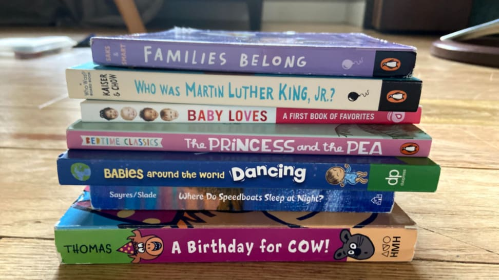 Stack of seven multi-colored children's books on a tan hard wood floor.