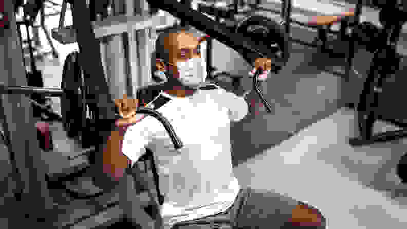 Man doing strength workout exercise in gym with face mask.