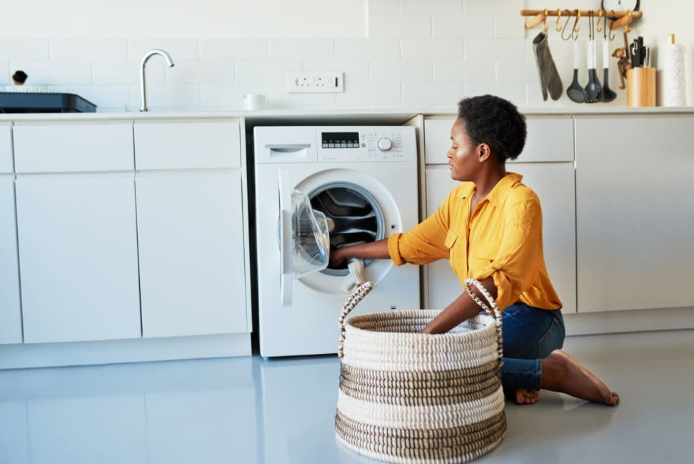 Woman wearing bright yellow shirt kneeling in front of a washing machine, removing clothes from it