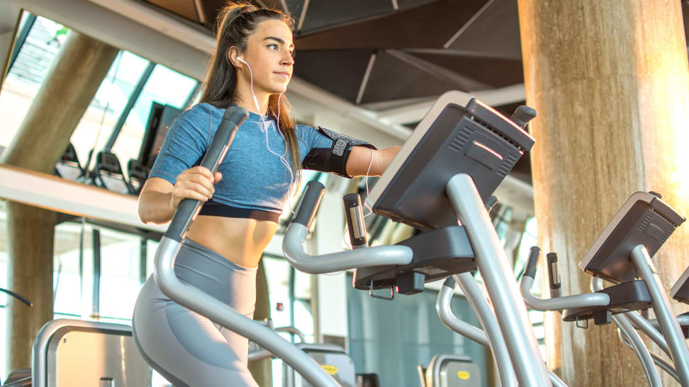 A woman using the elliptical machine at the gym.
