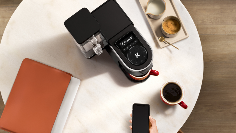 On a white marble coffee table, there's a Keurig K-Supreme Plus Smart pod coffee maker. Next to the machine, there's a coffee mug, a note book, and a tray of drinks. A person is pointing a smartphone at the machine, hinting the coffee maker's smart technology.