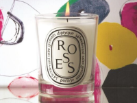 A lit Diptyque candle sits on a table.