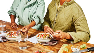 Two people dig into a meal of burrito bowls with tortilla chips on the side.