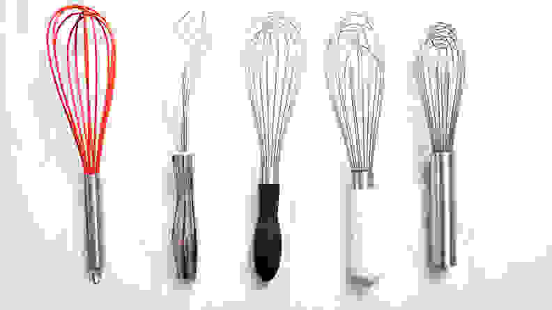 An assortment of whisks arranged on a marble countertop.