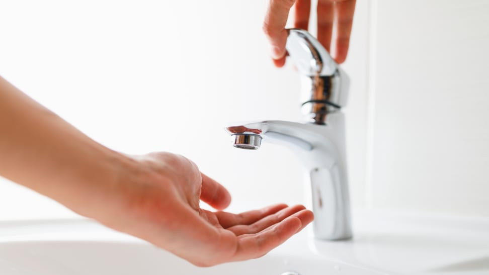 A hand opening sink faucet, using other hand to wait for water underneath, but no water is coming out