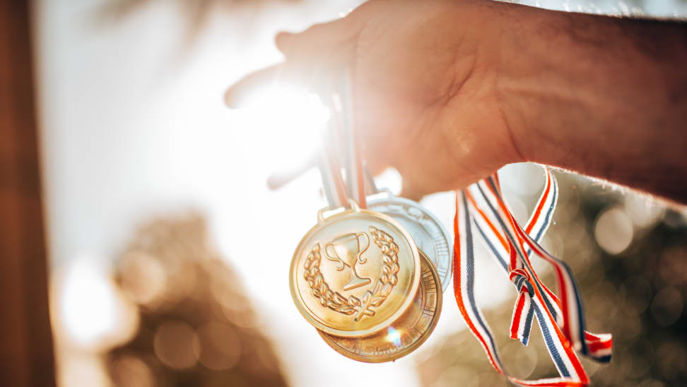 A person holding a fistful of gold medals.