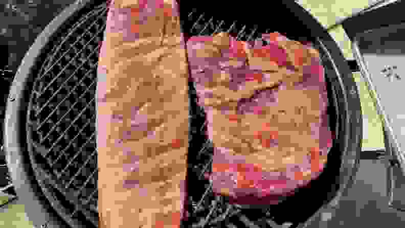 An uncooked rack of ribs and a roast sit on the grate of a charcoal grill, ready to be smoked.