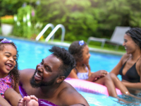 A family plays together in a swimming pool.