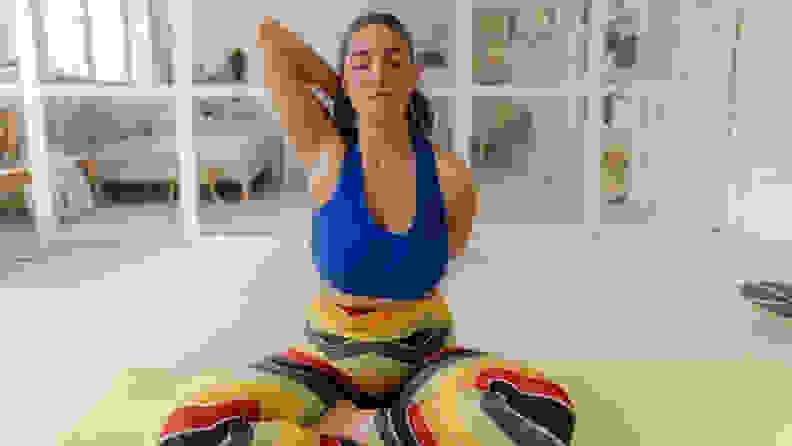 Photo of a young woman exercising in the living room of her apartment; maintaining healthy habits during Covid19 pandemic