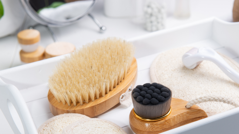 A brush laying next to other skincare tools on top of a vanity