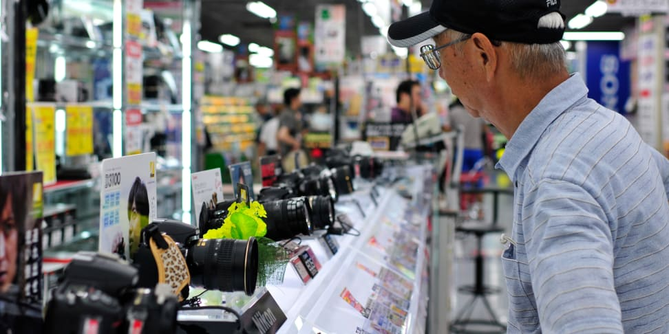 A shopper considers various lenses on display at a camera store