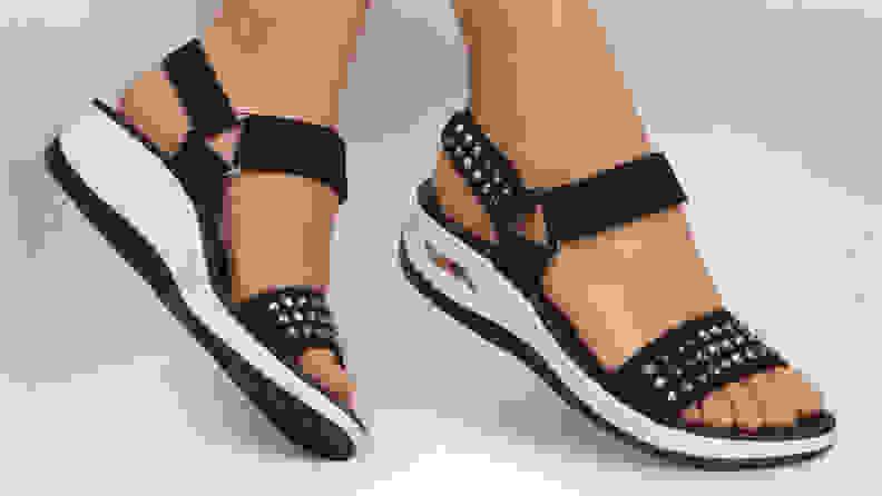 Woman wearing black sandals with legs crossed.