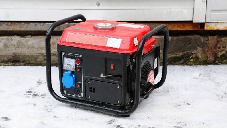 A red portable generator sitting on snow next to house
