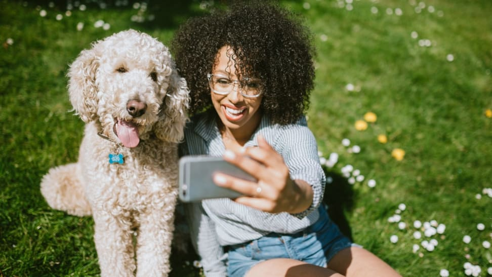 Woman talking selfie with dog in park