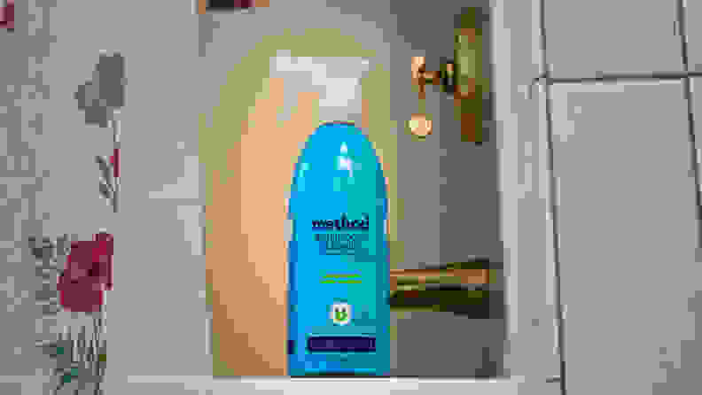 The Method cleaner stands on the edge of a tub's lip.