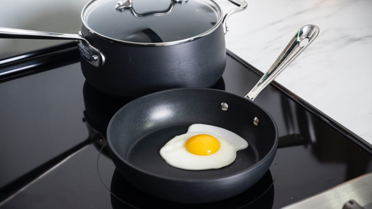 A perfect fried egg inside a nonstick pan, with a nonstick pot behind it, both sitting on a stovetop.