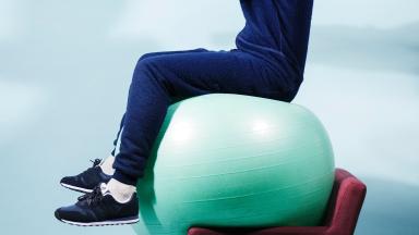 A performance artist balances on an exercise ball and a chair.
