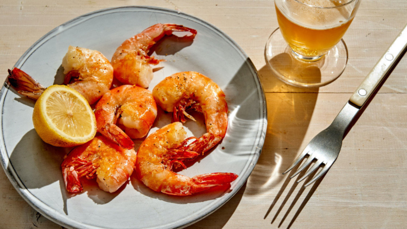 In a well-lit room, a plate of cooked shrimp is on display, accompanied by a fork and a glass of beer.