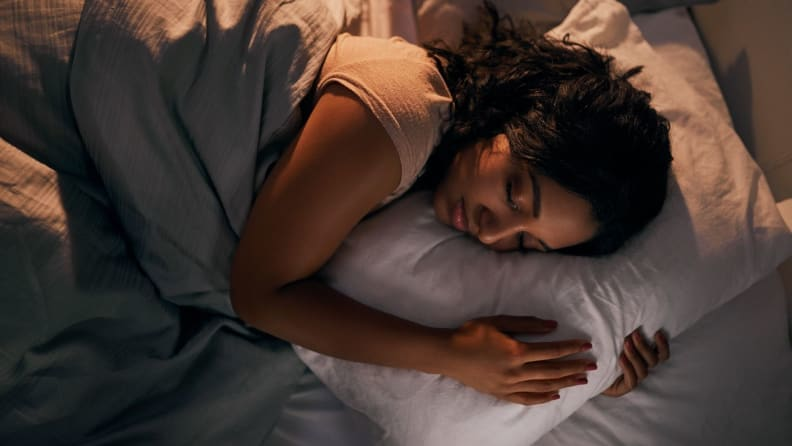 a woman curled up on her pillow in bed