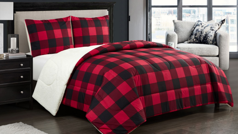 An image of a bed set with sherpa-lined red plaid blankets and pillowcases.