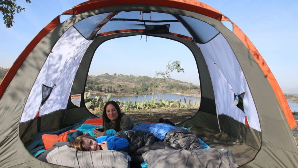 Young child and mother in a camping tent overlooking a lake with cactuses.