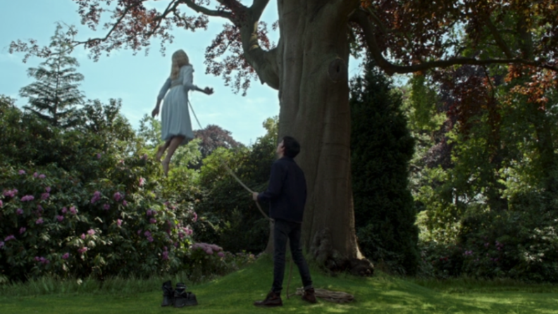A still from 'Miss Peregrine's Home for Peculiar Children' featuring Jake holding Emma to the earth by a rope.