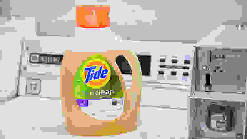 A bottle of Tide Purclean laundry detergent on a white top-loader washing machine.