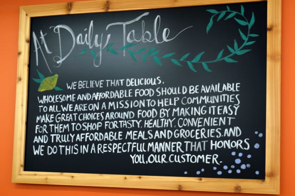 Daily Table's mission statement is proudly displayed on an artfully designed chalkboard sign.