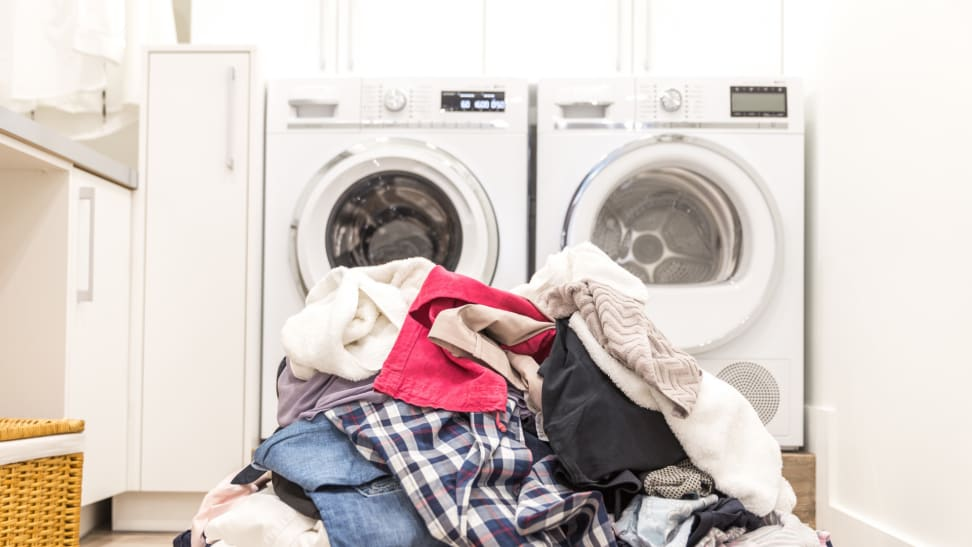 Pile of dirty laundry in front of a washer and dryer set