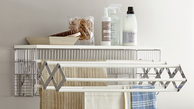 Pottery Barn's collapsible drying rack provides extra storage space for spray bottles, clothespins, and other necessities.
