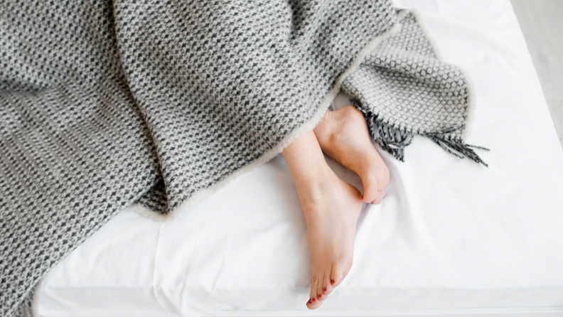 A pair of feet sticks out from under a grayish comforter near the edge of a bed.