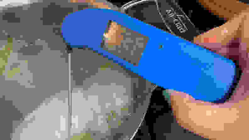 A person is poking a Thermapen ONE digital meat thermometer in Blue into a piece of poached chicken in a large pot.