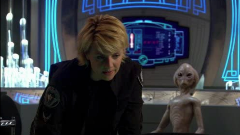 A still from 'Stargate SG-1' featuring a soldier and an alien.