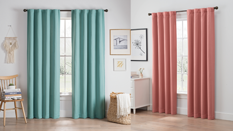 A set of teal curtains and a set of salmon-colored curtains hung up.