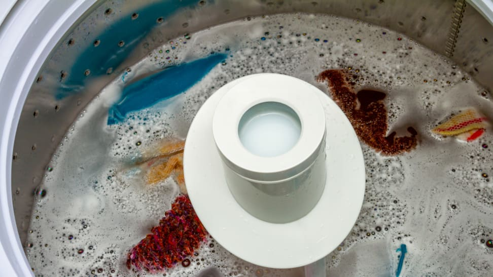 Basin of washing machine with an agitator pole. Basin is filled with soapy water and linens.