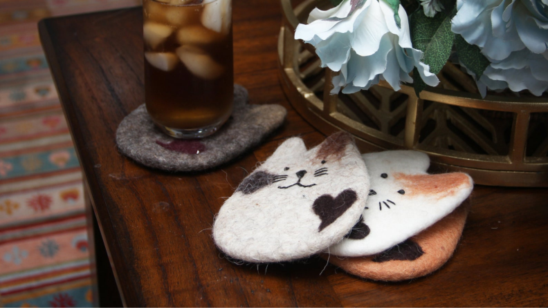 An image of three cat coasters stacked together on a tabletop.