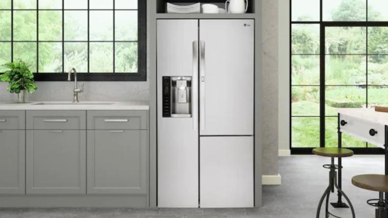 LG fridge next to grey cupboards.