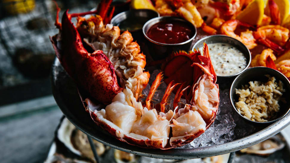 On a tray filled with crushed ice, there lies a half lobster and three little bowls of dipping sauces.