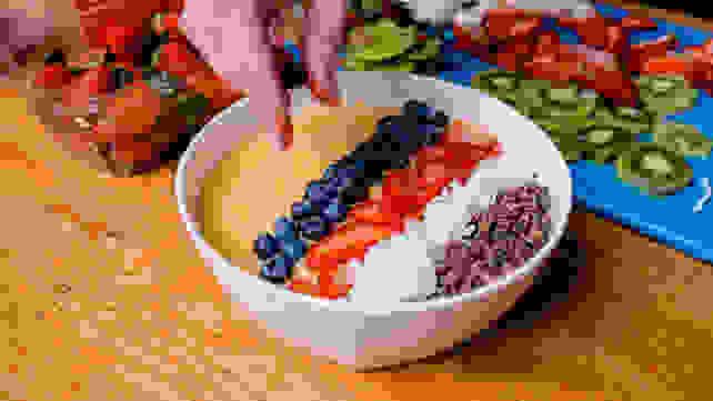 Adding blueberries to smoothie bowl