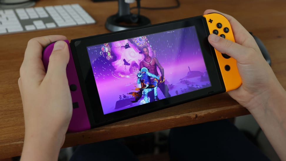 Person holds a Nintendo Switch while playing Fortnite