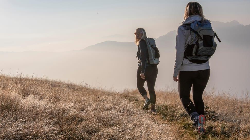 Women hiking through grassy field.