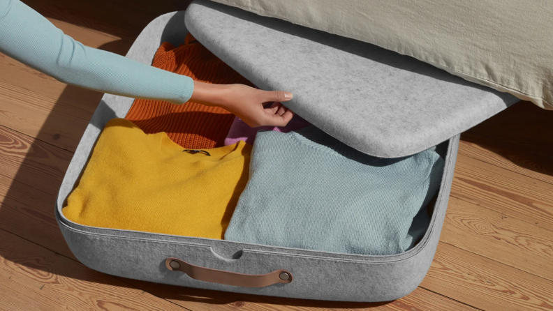 Woman's hand closing up under bed storage container filled with sweaters.