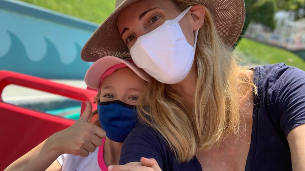 A young girl and a her mom both wearing masks and hats on a Disneyland ride