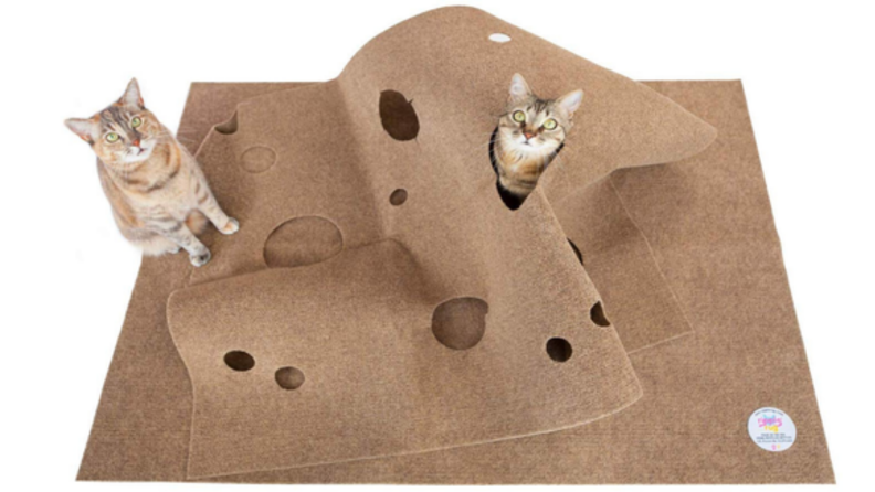 An image of cats playing in a rippled, holey rug.