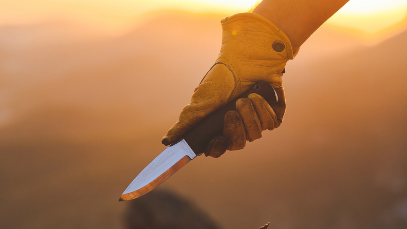 A person wearing gloves holds a knife outside.