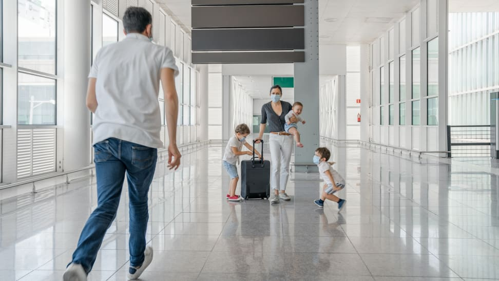 A family with three children in an airport pushing a suitcase