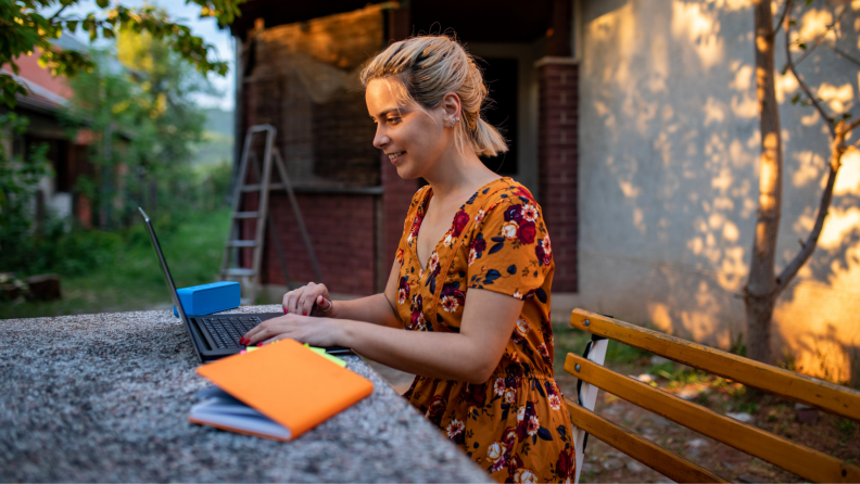 Woman sitting in front of computer outside smiling, next to blue portable speaker and orange notebook.