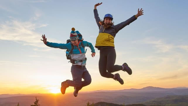 Two people jumping in L.L.Bean clothes on a mountain