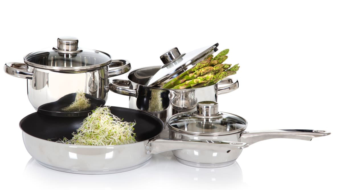 A cookware set, with vegetables in two of the pots.