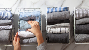 Two hands organizing clothes by using wire baskets.